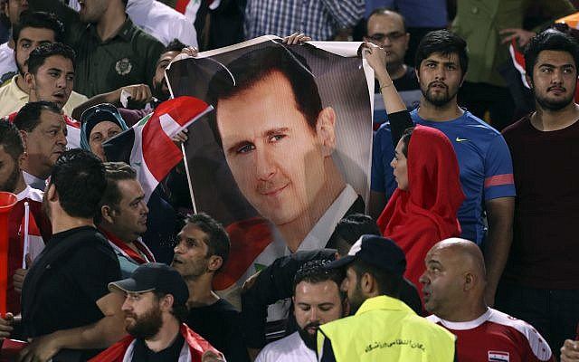 In this September 5, 2017 file photo, Syrian soccer fans hold a portrait of their president, Bashar Assad, before their match with Iran during a Round 3 - Group A World Cup qualifier at the Azadi Stadium in Tehran, Iran. (AP Photo/Vahid Salemi, File)