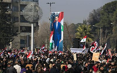 In this January 19, 2017, file photo, pro-government supporters hold up the Syrian flag and pictures of Syrian President Bashar Assad at a gathering at Saadallah al-Jabiri Square in Aleppo, Syria. (AP Photo/Hassan Ammar, File)