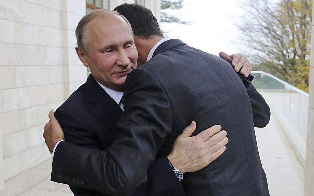 Russian President Vladimir Putin, left, embraces Syrian President Bashar Assad in the Bocharov Ruchei residence in the Black Sea resort of Sochi, Russia, November 20, 2017. (Mikhail Klimentyev, Kremlin Pool via AP)