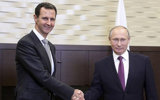 Russian President Vladimir Putin, right, shakes hand with Syrian President Bashar Assad in the Bocharov Ruchei residence in the Black Sea resort of Sochi, Russia, November 20, 2017. (Mikhail Klimentyev, Kremlin via AP)