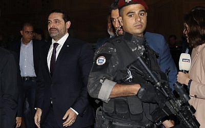 Lebanese Prime Minister Saad Hariri, center, escorted by his bodyguards walks to pray over his father's grave, upon his arrival to Beirut, Lebanon, Tuesday, November 21, 2017. (AP Photo/Hussein Malla)
