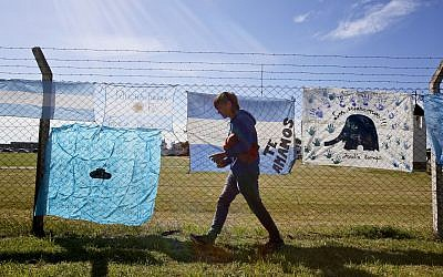 A brother of submarine crew member Diego Wagner walks away after placing a national flag in support of his brother and other crew members of the missing ARA San Juan, on a fence enclosing the Mar del Plata Naval Base, in Argentina, November 23, 2017. (AP Photo/Esteban Felix)