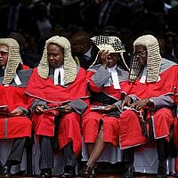 A senior judge uses a fan to shield her face from the sun as she sits with others at the inauguration ceremony of President Emmerson Mnangagwa in the capital Harare, Zimbabwe Friday, November 24, 2017. (AP Photo/Ben Curtis)