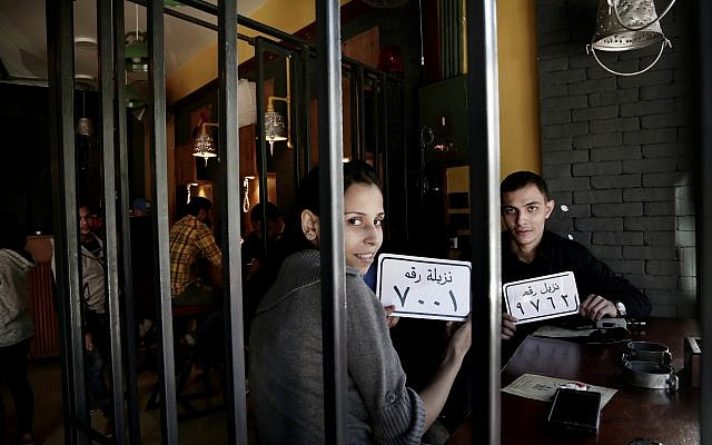 In this Nov. 22, 2017 photo, customer Amr El Gohary, right, and his friend pose for a photograph with plastic plaques with inmate numbers as they wait for their food at the prison-themed restaurant 'Food Crime' in the Nile Delta city of Mansoura, 110 kilometers (70 miles) north of Cairo, Egypt. (AP Photo/Nariman El-Mofty)