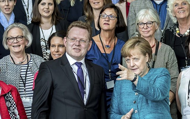 In This May 17, 2017 file photo, German Chancellor Angela Merkel talks to the mayor of the western German town of Altona, Andreas Hollstein, center, during the award ceremony for the German national integration prize. (Michael Kappeler/dpa via AP)
