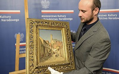 A museum worker carries a 19th century painting during a presentation ceremony in Warsaw, Poland on November 29, 2017. (AP Photo/Alik Keplicz)