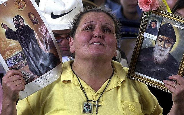 Mary Iskandar, 50, a Lebanese housewife, is overcome by emotion, as she raises a picture of Maronite Naamatallah Kassab Hardini, left, and St. Charbel Makhlouf, Lebanon's first Maronite cleric to be canonized by the Vatican, in 1977, as Pope John Paul II, proclaims Hardini a saint of the Catholic Church at a ceremony at the Vatican on May 16, 2004.  (AP Photo/Mahmoud Tawil)