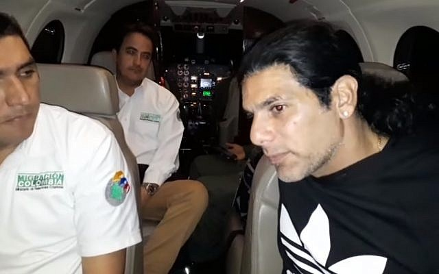 Screen capture from video showing alleged crime lord Assi Ben-Mosh, right, on a flight after being expelled from Colombia. (Screen capture: YouTube)