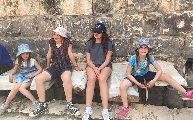 Tourists at Israel's Beit Sh'ean National Park test drive the Roman-era public latrine, March 2017. (Amanda Borschel-Dan/Times of Israel)