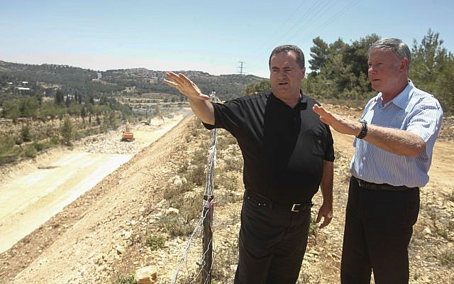 Israel's Transporation Minister Yisrael Katz, center, stands with Netivei Israel CEO Shai Baras, later arrested for cronyism, as they inspect the construction of a new highway between Jerusalem and Tel Aviv, on June 12, 2013. (Flash 90)