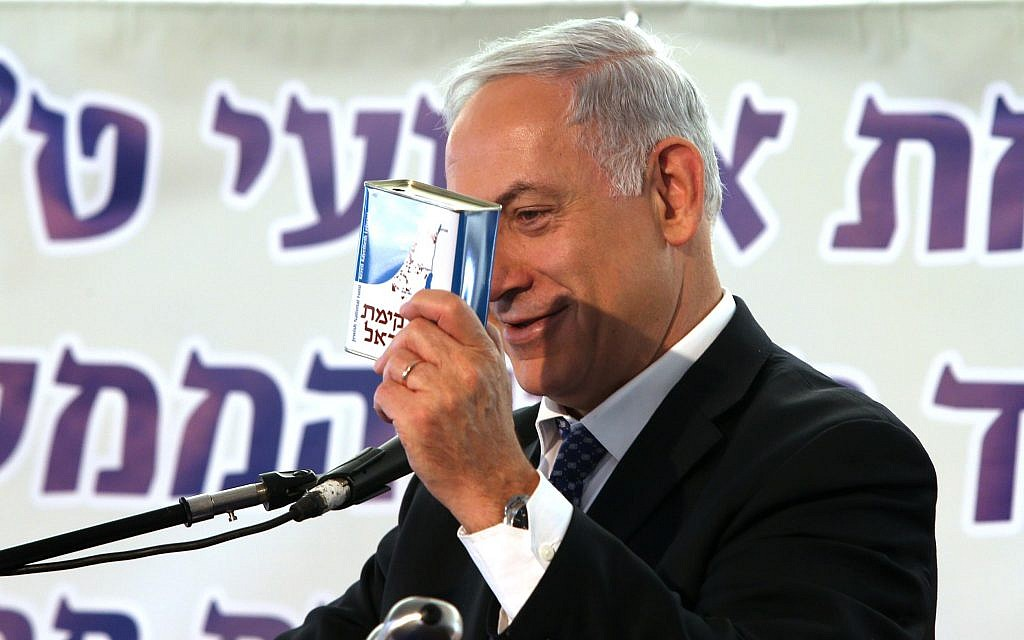 Prime Minister Benjamin Netanyahu holding KKL-JNF collection box at a tree planting ceremony in the Jerusalem forest on January 15, 2014. (Amit Shabi/Pool/Flash 90)