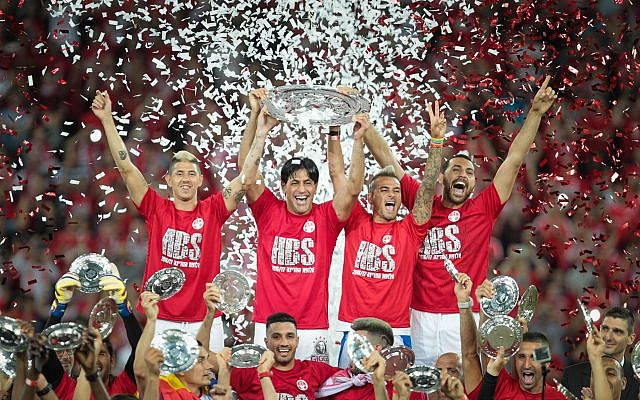 Hapoel Beersheba captain Elyaniv Barda, second from left, together with other members of the soccer team, celebrating after winning at the Israeli soccer league championship at the Turner Stadium in Beersheba, May 8, 2017. (Roy Alima/Flash90)