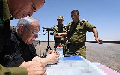 Prime Minister Benjamin Netanyahu and senior IDF officers tour the northern border, in the Israeli Golan Heights, on July 25, 2017. (Kobi Gideon / GPO)