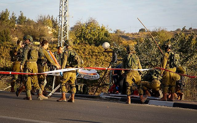 Israeli security and medical personnel evacuate a wounded Palestinian terrorist at the scene of ramming and stabbing attack near the Gush Etzion Junction on November 17, 2017. (Gershon Elinson/Flash90)