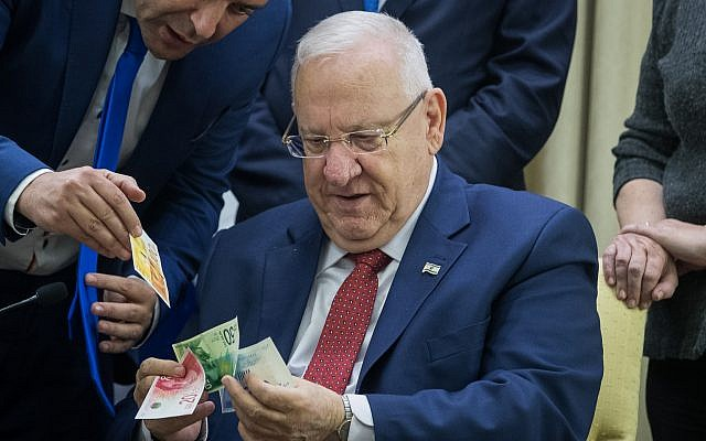 President Reuven Rivlin looks at the new NIS 20 and NIS 100 bills at a ceremony in his residence in Jerusalem on November 22, 2017. (Yonatan Sindel/Flash90)
