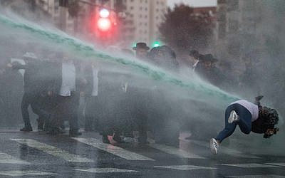 A jet of anti-riot skunk water sends a woman reeling as ultra-Orthodox Jews protest the jailing of draft dodgers, Jerusalem, November 27, 2017. (Flash90)