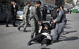 Ultra-Orthodox Jewish men clash with police during a protest against the arrest of a religious seminary student who failed to comply with a recruitment order, next to the army draft office in Jerusalem, November 28, 2017. (Flash90)