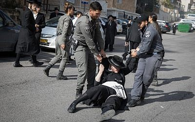 Ultra-Orthodox Jewish men clash with police during a protest against the arrest of a religious seminary students who failed to comply with a recruitment order, next to the army draft office in Jerusalem, November 28, 2017. (Flash90)