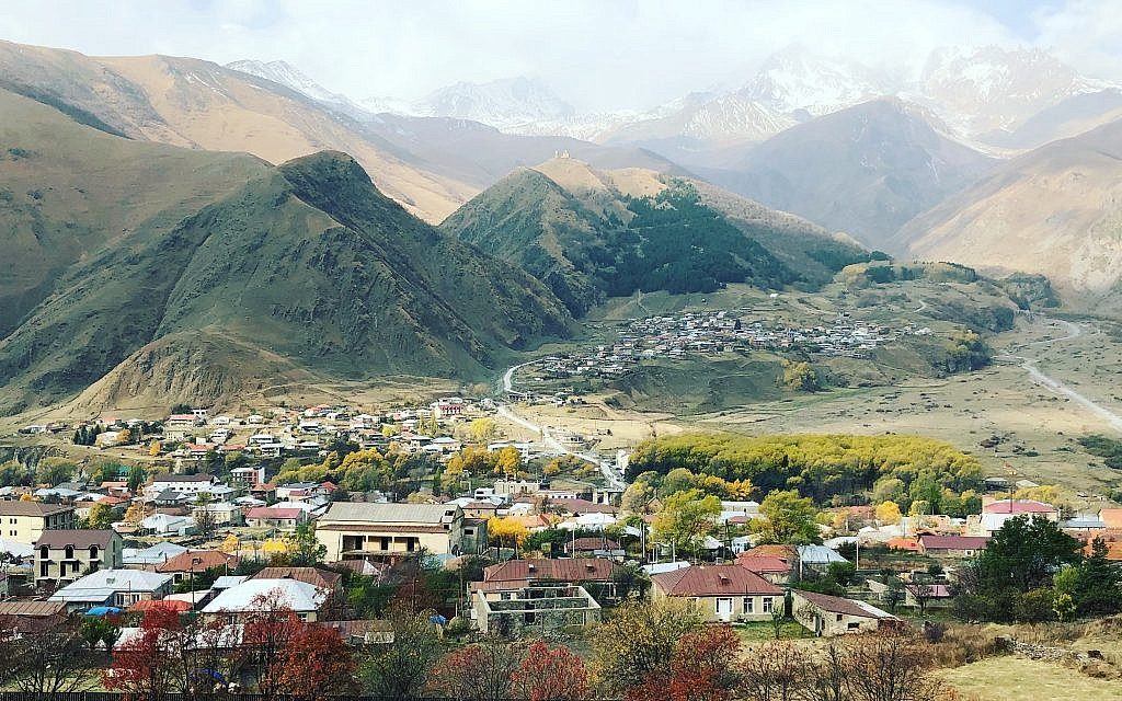 A view of Mount Kazbegi and the Gergeti Church overlooking the Georgian village of Kazbegi (Jessica Steinberg/Times of Israel)