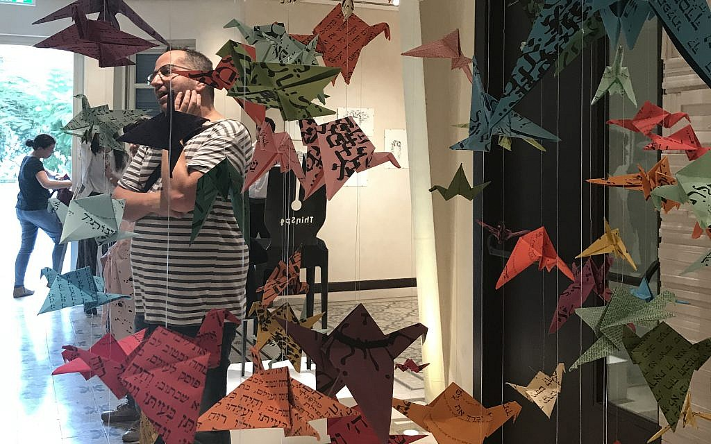 Curator Yuval Saar at an Illustration Week exhibit Grace Austin/Times of Israel)