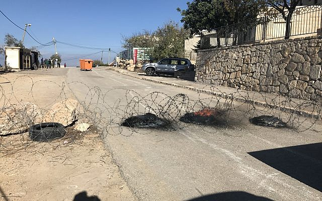 Israeli settlers set up burning barricades and barbed wire to prevent security forces from evacuating them from the illegal Netiv Ha'avot outpost in the West Bank, November 29, 2017 (Jacob Magid/Times of Israel)