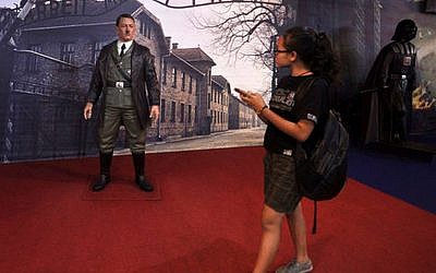In this Wednesday, Nov. 8, 2017 photo, a visitor walks past the wax figure of Adolf Hitler displayed against the backdrop of an image of Nazi Death Camp Auschwitz-Birkenau next to Star Wars character Darth Vader, right, at De Mata Museum in Yogyakarta, Indonesia. (AP Photo/Slamet Riyadi)
