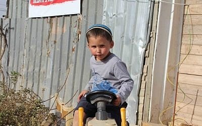A child of Netiv Avot, where 17 homes are slated for destruction in March 2018. The sign behind him says, 'No more destruction; normalize Netiv Avot.' (Laura Ben-David)