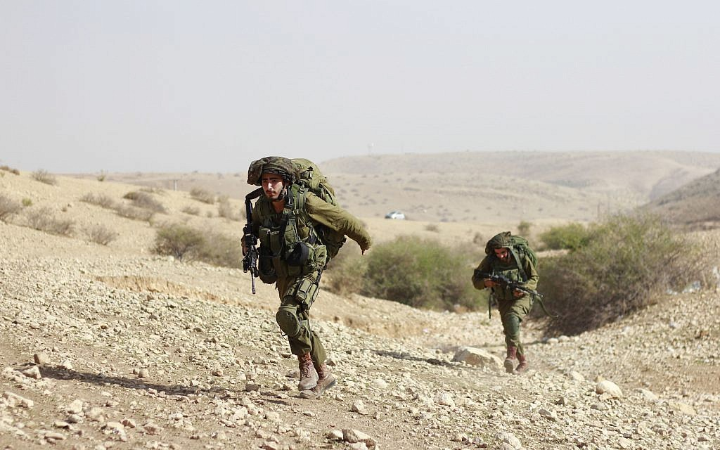 Soldiers from the IDF's Kfir Brigade run to capture a hill during a training exercise in the Jordan Valley on November 28, 2017. (Judah Ari Gross/Times of Israel)