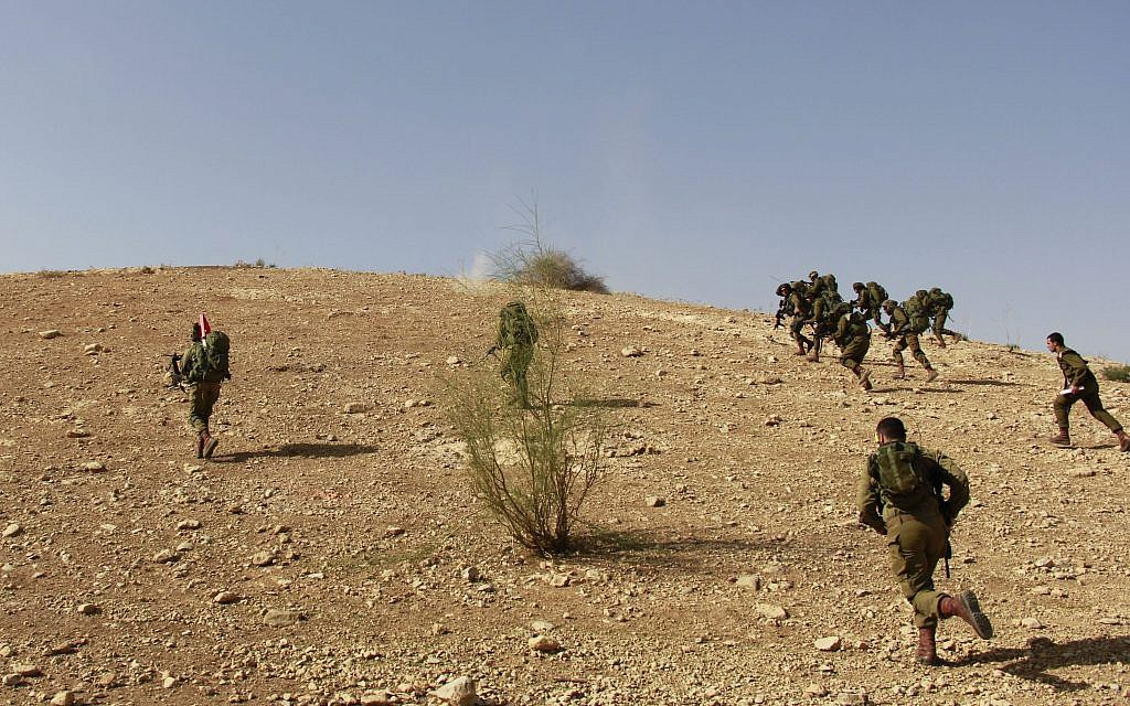 Cpt. Sofar Ganem, bottom right, and his soldiers from the IDF's Kfir Brigade run to capture a hill during a training exercise in the Jordan Valley on November 28, 2017. (Judah Ari Gross/Times of Israel)