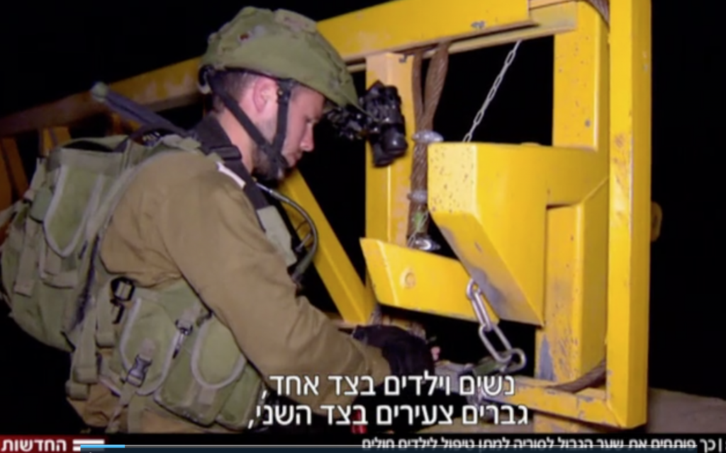 Israeli soldiers open a gate at the Syrian border ahead of the entry of a group of Syrian mothers and children for medical treatment, November 2017 (Hadashot TV screenshot)