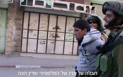 Footage of Dean Issacharoff (right) leading away a Palestinian in Hebron in March 2014. (Screen Capture/B'Tselem)
