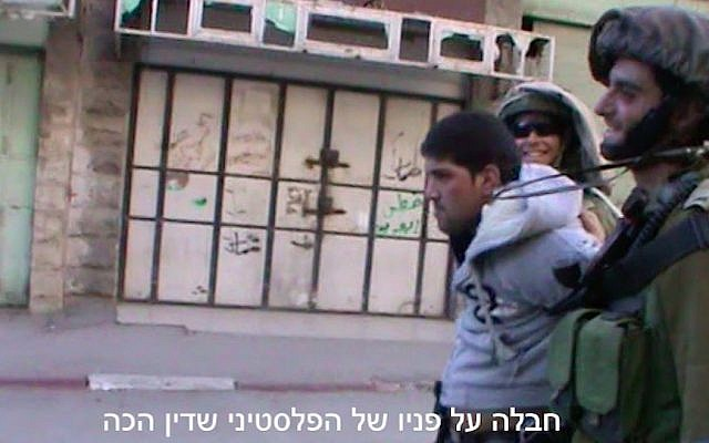 Footage of Dean Issacharoff (right) leading away a beaten Palestinian in Hebron in March 2014. (Screen Capture/B'Tselem)