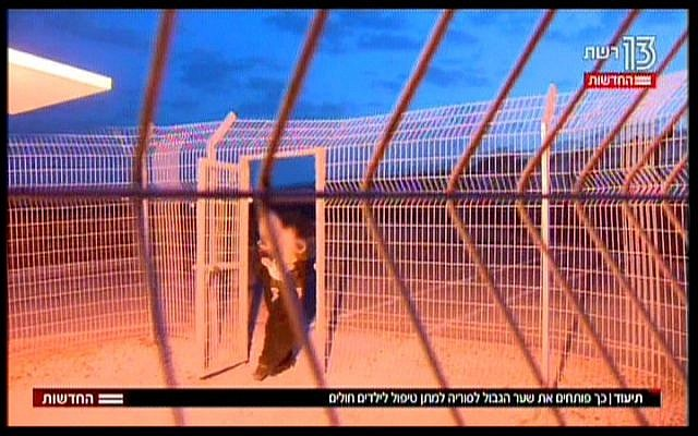 A Syrian mother, carrying her young child, crosses the border into Israel, in a TV report broadcast on November 19, 2017. (Hadashot News screenshot)