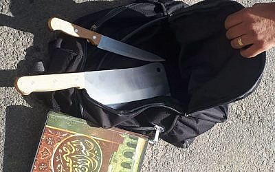A meat cleaver, knife, and copy of the Quran, found in the backpack of a Palestinian man, who said they were going to be used in a terror attack near the Kochav Yaakov settlement in the central West Bank on November 9, 2017. (Israel Police)