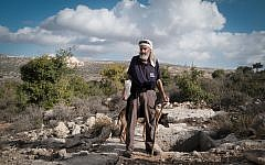 Avraham Herzlich stands next to an ancient mikveh in the fields near his home in Kfar Tapuah. (Luke Tress/Times of Israel)