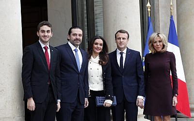 French President Emmanuel Macron, center right, and his wife Brigitte, right, greet Lebanon's Prime Minister Saad Hariri, second left, his wife Lara, center left, and their son Hussam upon their arrival at the Elysee Palace in Paris, November 18, 2017. (AP Photo/Christophe Ena)