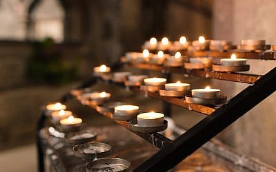 Tealight candles in a church lit for prayer and remembrance. (iStock)