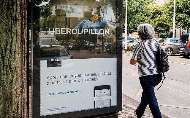 Uber advertising for taxi service at bus station (Credit: AdrianHancu, iStock by Getty Images)