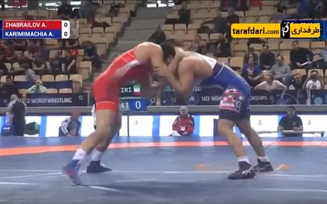 Iranian wrestler Alireza Karimi leading his match against Russia's Alikhan Zhabrailov 3-2, when his coach can be heard from the sidelines instructing him to lose, at the World Championships in Poland, November 25, 2017. (screen capture: YouTube)