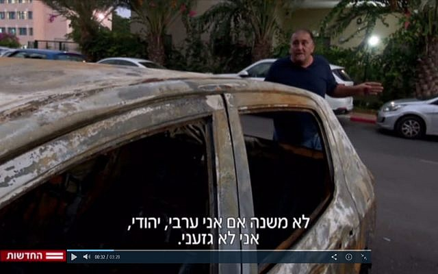 Yoram Israeli stands next to his torched car in Netanya on November 3, 2017. (Screen capture Channel 2)