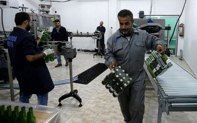 Employees of Arados brewery work on the production line at their plant in the northwestern Syrian city of Safita, southeast of Tartous on November 15, 2017. (AFP Photo/Louai Beshara)