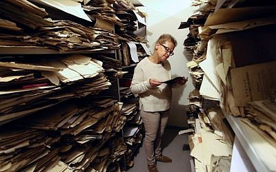 Judaica Research Centre chief Lara Lempertiene stands amid rediscovered Jewish documents, long thought to have been destroyed during World War II, at the Lithuanian national library in Vilnius on November 3, 2017. (AFP/Petras Malukas)