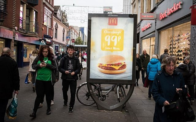 People walk by an advertisement for McDonald's in Nottingham, England, on November 17, 2017. (AFP Photo/Oli Scarff)