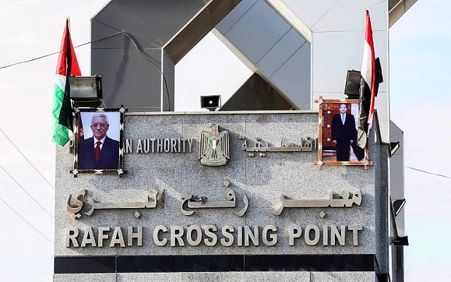 This file photo taken on November 1, 2017, shows portraits of Egyptian President Abdel Fattah el-Sissi and PA President Mahmoud Abbas hanging at the Rafah border crossing with Egypt. (AFP Photo/Said Khatib)