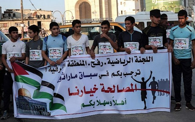 """This file photo taken on November 27, 2017, shows Palestinian youths holding a banner reading """"reconciliation is our choice,"""" at an event organized by Hamas' sports committee, in the southern Gaza town of Rafah. (AFP Photo/Said Khatib)"""