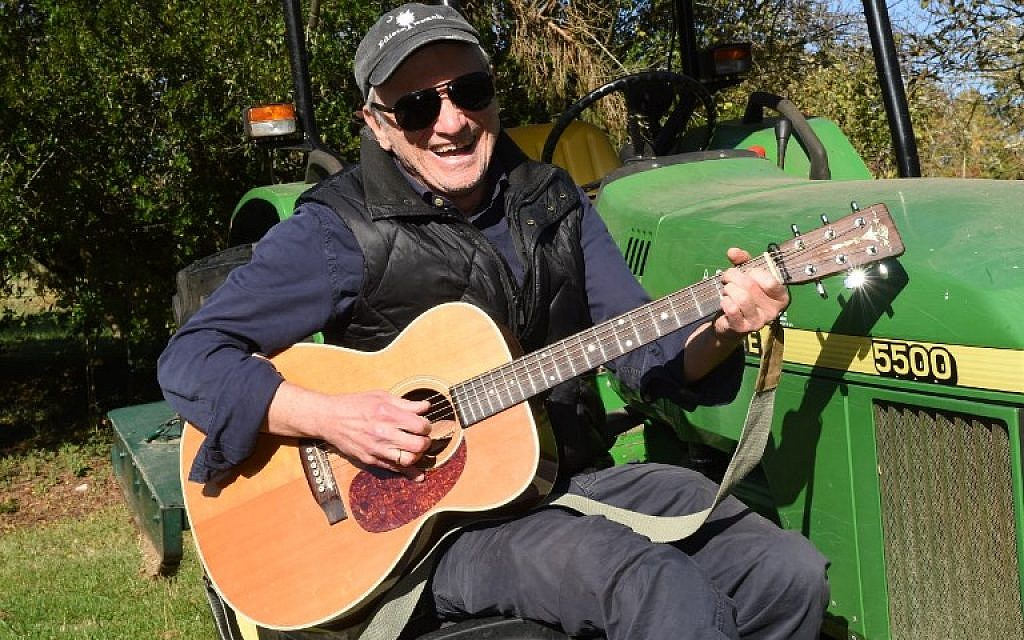 This photo taken on November 14, 2017 shows US country musician Daniel Antopolsky playing guitar on a tractor in Fargues-Saint-Hilaire, near Bordeaux, southwestern France where he settled down in the 90s. (AFP PHOTO / MEHDI FEDOUACH)