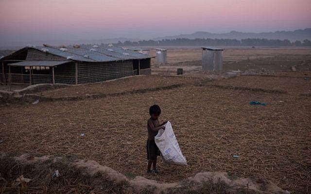 A Rohingya boy gathers grass stalks at the Naybara refugee camp, in Cox's Bazar on December 3, 2017. (AFP Photo/Ed Jones)