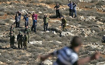 Palestinian men throw stones toward Israeli soldiers and settlers at the entrance to the northern West Bank village of Qusra on December 4, 2017. (AFP Photo/Jaafar Ashtiyeh)