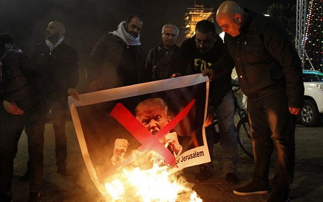Palestinian protesters burn pictures of US President Donald Trump at Bethlehem's Manger Square on December 5, 2017. (AFP Photo/Musa Al Shaer)