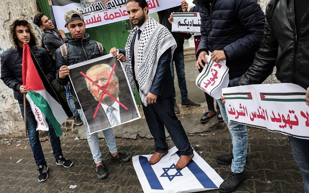 Palestinian protesters prepare to burn a picture of US President Donald Trump in the southern Gaza Strip town of Rafah on December 6, 2017, ahead of US President Donald Trump's expected announcement recognizing Jerusalem as Israel's capital. (AFP PHOTO / SAID KHATIB)